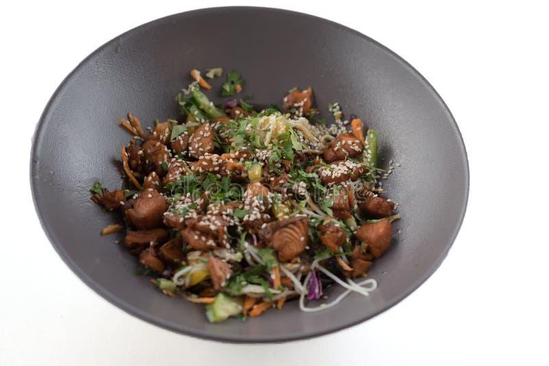 Gesunder Gemüsesalat mit Lachsen auf dem grauen modernen Teller lokalisiert auf weißem Hintergrund lizenzfreies stockfoto