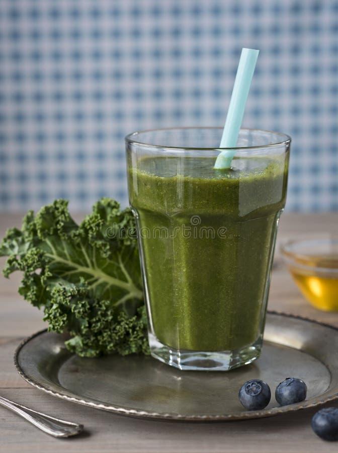 Gesunder grüner Smoothie mit Kohl, Blaubeeren und Honig in einem Glas gegen einen rustikalen hölzernen Hintergrund lizenzfreie stockfotos