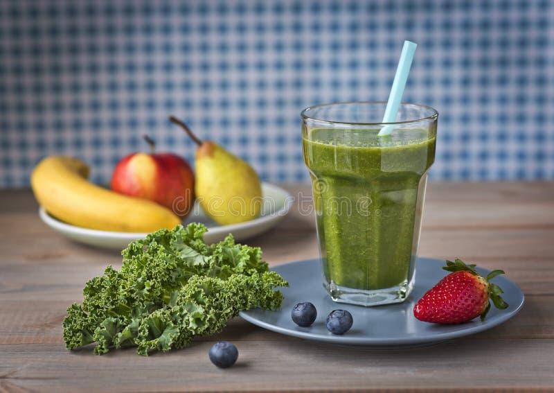 Gesunder grüner Smoothie mit Kohl, Erdbeeren, Blaubeeren, Banane, Apfel, Birne und Honig in einem Glas gegen ein rustikales hölze stockbild