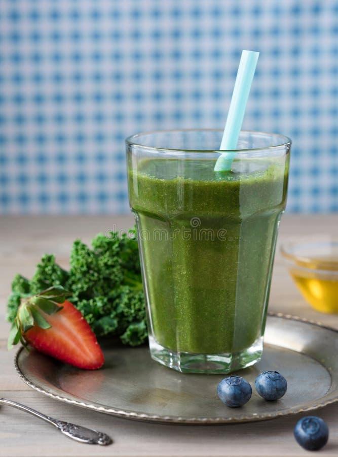 Gesunder grüner Smoothie mit Kohl, Erdbeeren, Blaubeeren und Honig auf einer Weinleseplatte in einem Glas gegen ein rustikales hö lizenzfreie stockfotos