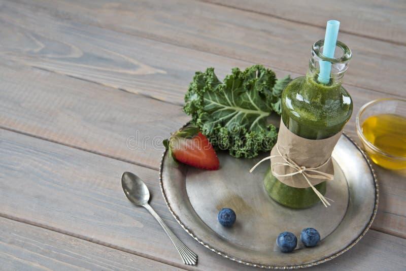 Gesunder grüner Smoothie mit Kohl, Erdbeeren, Blaubeeren und Honig in der Flasche mit Aufkleber auf rustikalem hölzernem Hintergr stockbilder