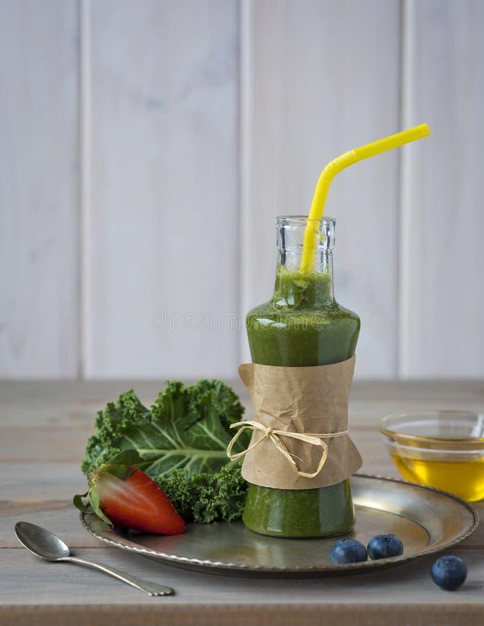 Gesunder grüner Smoothie mit Kohl, Erdbeeren, Blaubeeren und Honig in der Flasche mit Aufkleber auf rustikalem hölzernem Hintergr stockfotos