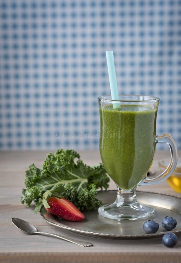 Gesunder grüner Smoothie mit Kohl, Erdbeeren, Blaubeeren und Honig in einem Glas gegen einen rustikalen hölzernen Hintergrund lizenzfreies stockbild