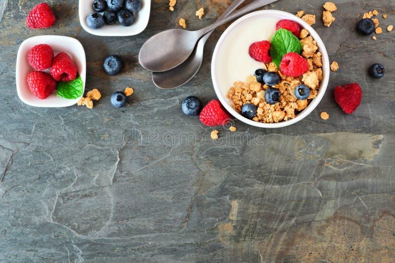Gesunder Jogurt mit Beeren und Granola, Spitzengrenze über einem dunklen Hintergrund lizenzfreie stockfotos