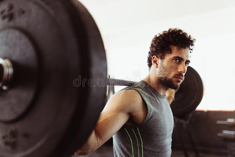 Gesunder junger Kerl an der Turnhalle trainierend mit Barbell lizenzfreie stockfotografie