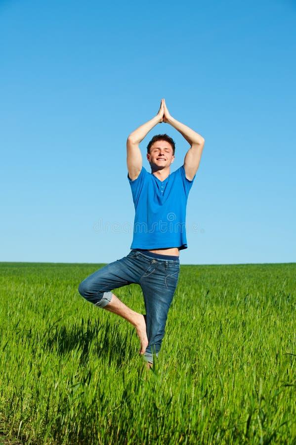 Gesunder junger Mann, der Yoga gegen Himmel tut stockbilder