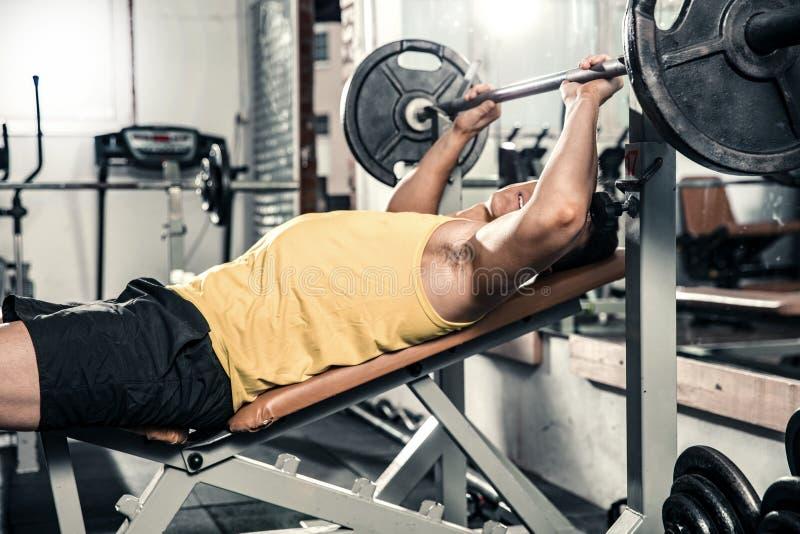 Gesunder junger Mann führt Übungen auf dem Kasten durch stockbild