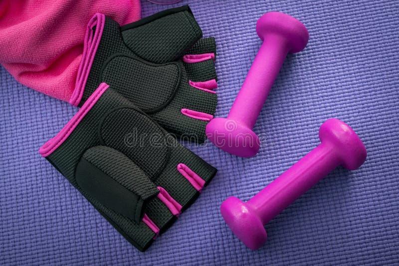 Gesunder Lebensstil, Eignungs- und Yogakonzept mit girly Trainingsausrüstung wie einem rosa Paar Turnhallenhandschuhen, zwei Dumm stockfoto