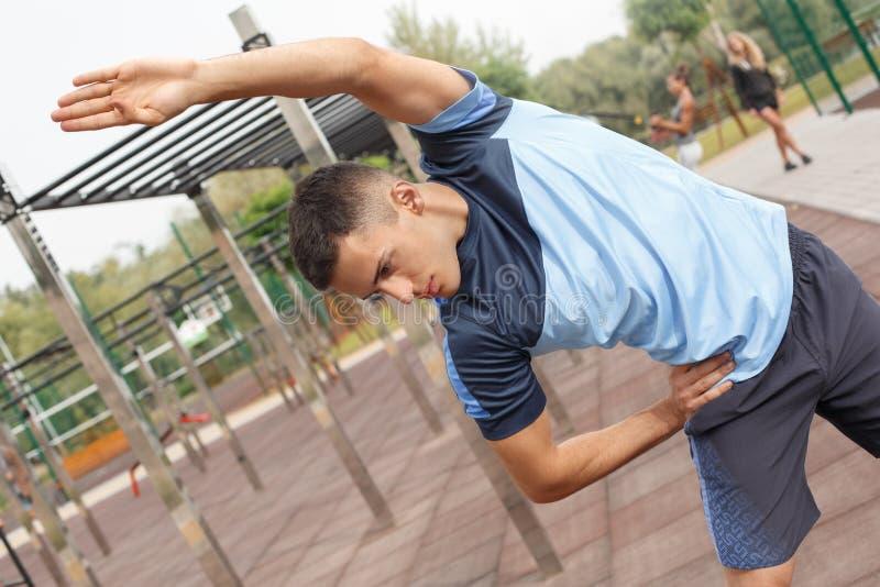 Gesunder Lebensstil Junger Mann, der draußen sich lehnen zur rechten durchdachten Nahaufnahme ausübt lizenzfreies stockbild