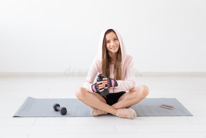 Gesunder Lebensstil, Leute und Sportkonzept - l?chelnde Frau, die auf Yogamatte und Trinkwasser nach hartem Training sitzt stockfotos