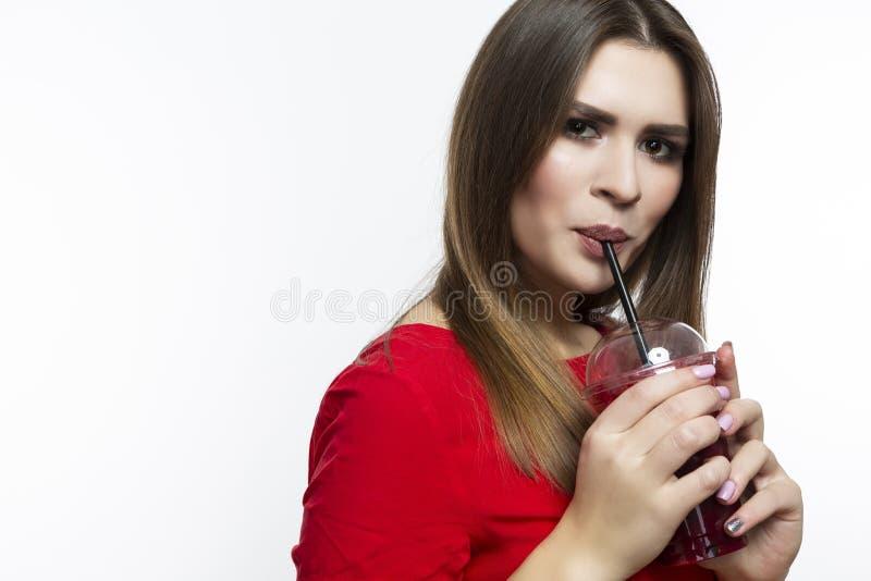 Gesunder Lebensstil Positives lächelndes Mädchen, das roten Smoothie Juice Mix trinkt Aufstellung im roten Kleid über weißem Hint lizenzfreies stockfoto