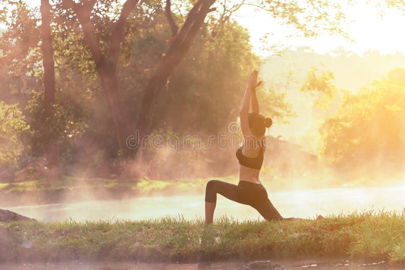 Gesunder Lebensstil Silhouettieren Sie Meditationsyogafrau für sich entspannen wesentliches und Energie morgens am Park der heiße lizenzfreies stockbild
