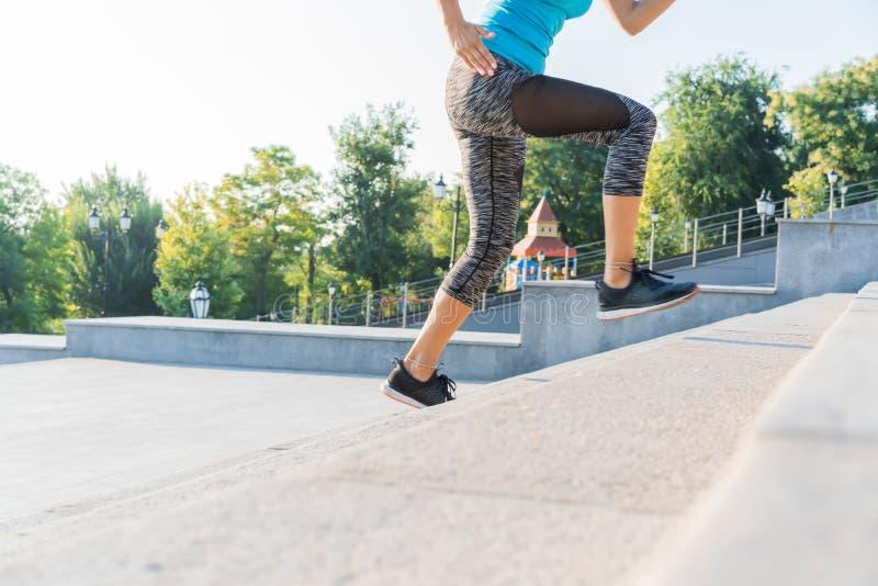 Gesunder Lebensstil trägt die Frau zur Schau, die oben auf Steintreppensonnenaufgangküste läuft lizenzfreies stockbild