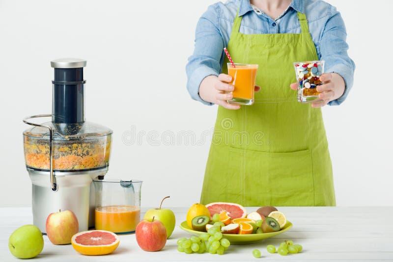 Gesunder Lebensstil und Diätkonzept Fruchtsaft, Pillen und Vitaminergänzungen, Frau, die eine Wahl trifft stockfotos