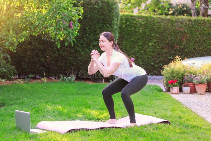 Gesunder Lebensstil Zu Hause trainieren Eignung online tun Sch?ne junge Frau, die drau?en Sport im Garten tut lizenzfreie stockbilder