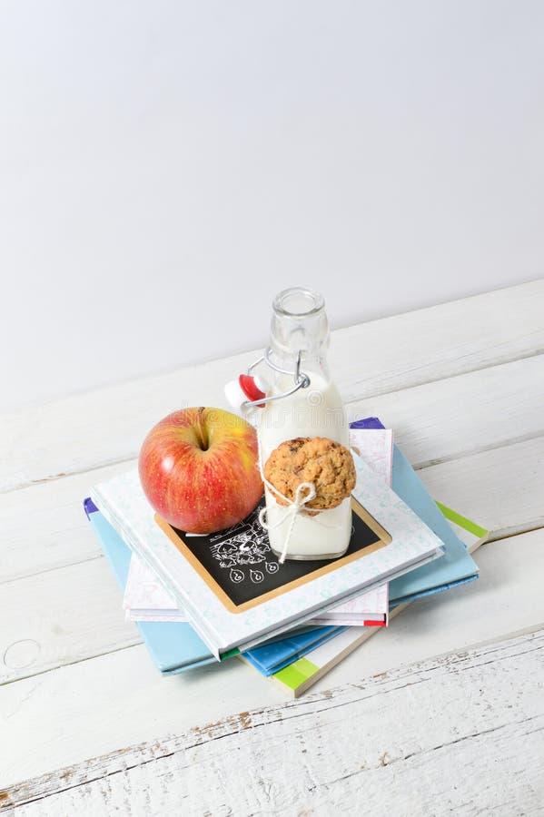 Gesunder Lunchbox mit Büchern und Milch lizenzfreie stockfotos