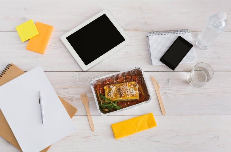 Gesunder Mittagessenfolienkasten mit Diätlebensmittel auf Bürotisch lizenzfreie stockfotografie