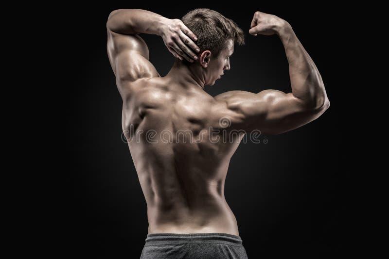 Gesunder muskulöser junger Mann, der zurück darstellen und Bizepsmuskeln lizenzfreie stockbilder