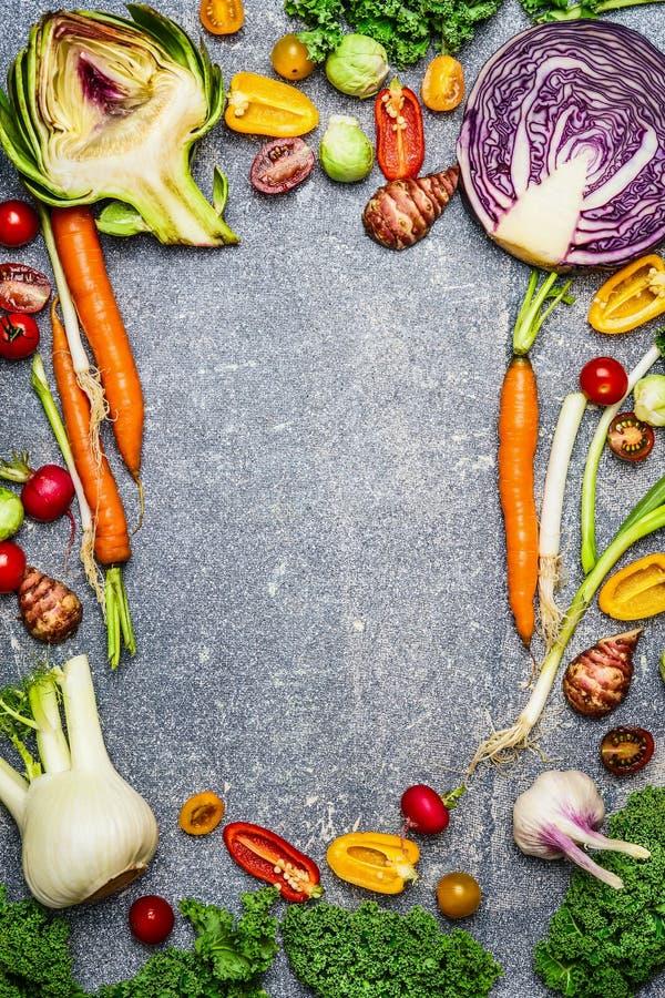 Gesunder oder vegetarischer Lebensmittelhintergrund mit Zusammenstellung des frischen Bauernhofgemüses auf grauem rustikalem Hint stockfotografie