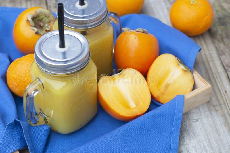 Gesunder Orangensaft mit Persimone, kakifarbige Fr?chte in den Glasgef??en, rustikaler Holztisch Kopieren Sie Platz lizenzfreies stockfoto