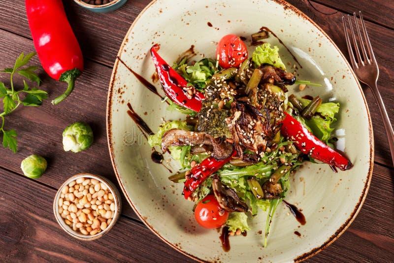 Gesunder Salat mit rucola, grüner Pfeffer, Tomaten, Zucchini, Brokkoli, Rosenkohl, Spargel, Sojabohnenöl auf hölzernem Hintergrun lizenzfreies stockfoto