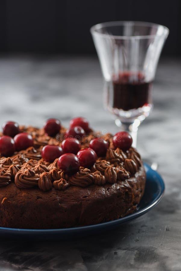 Gesunder schwach gezuckerter selbst gemachter Schokoladenkuchen mit Schokoladenzuckerglasur und rohen Kirschen diente mit Rotwein lizenzfreie stockfotografie