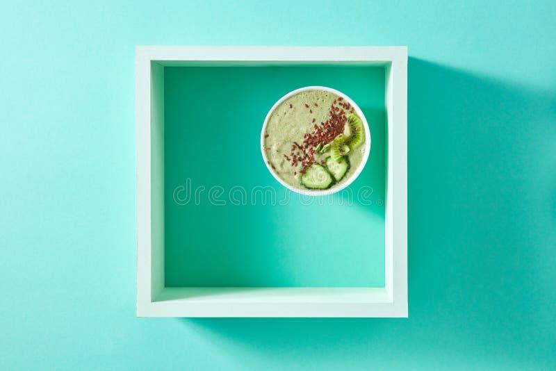 Gesunder Smoothie vom grünen Gemüse und von den Früchten mit Leinsamen in einer weißen Schüssel im quadratischen Rahmen auf einem stockfoto
