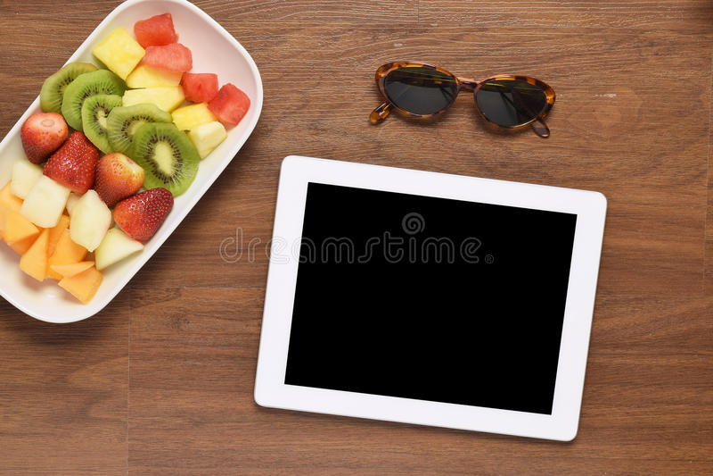 Gesunder Snack und Tablette auf hölzernem Schreibtisch stockbild