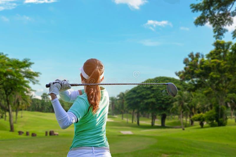 Gesunder Sport Der asiatische sportliche Frauengolfspielerspieler, der Golfschwingent-st?ck weg auf der gr?nen Gl?ttungszeit tut, stockbilder