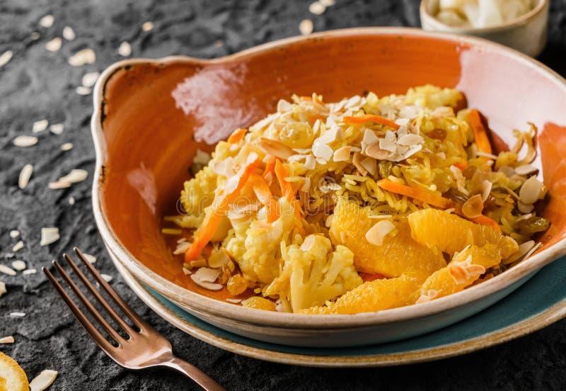 Gesunder Teller des strengen Vegetariers, gekochter Reis mit Rosinen, Blumenkohl, Orange und Mandeln in der keramischen Platte üb stockfotos