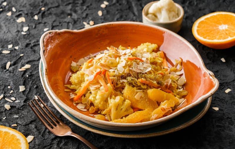 Gesunder Teller des strengen Vegetariers, gekochter Reis mit Rosinen, Blumenkohl, Orange und Mandeln in der keramischen Platte üb stockbilder