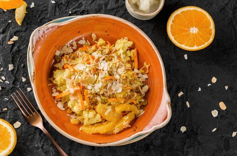 Gesunder Teller des strengen Vegetariers, gekochter Reis mit Rosinen, Blumenkohl, Orange und Mandeln in der keramischen Platte üb stockbild