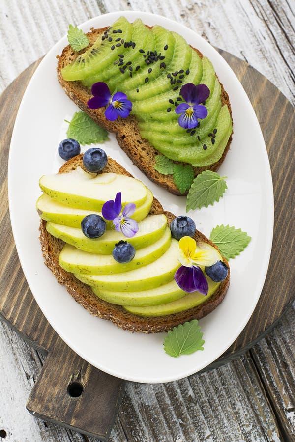 Gesunder Toast mit grünem Apfel und saftige Kiwi mit essbaren Blumen von Gartenviola auf einem Marmorhintergrund Farbjahr lizenzfreie stockfotos
