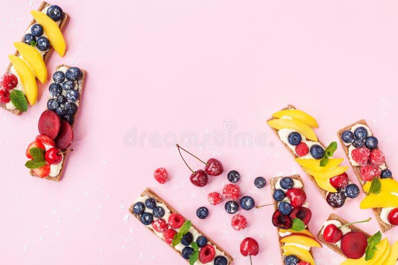Gesunder und Diätimbiß oder -nachtisch von den Sandwichen mit sahnigem Käse- und SommerBeerenobst auf Draufsicht des rosa modisch stockbilder