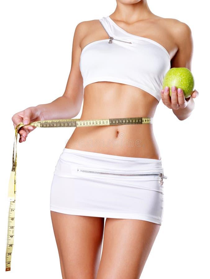 Gesunder weiblicher Körper mit Apfel und messendem Band. stockfotografie