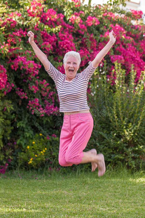 gesundes aktives älteres Frauenspringen lizenzfreies stockfoto