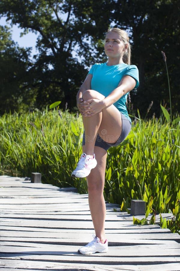 Gesundes blondes Mädchen, das ihre Beine auf Holzbrücke, Sommer ausdehnt stockbild