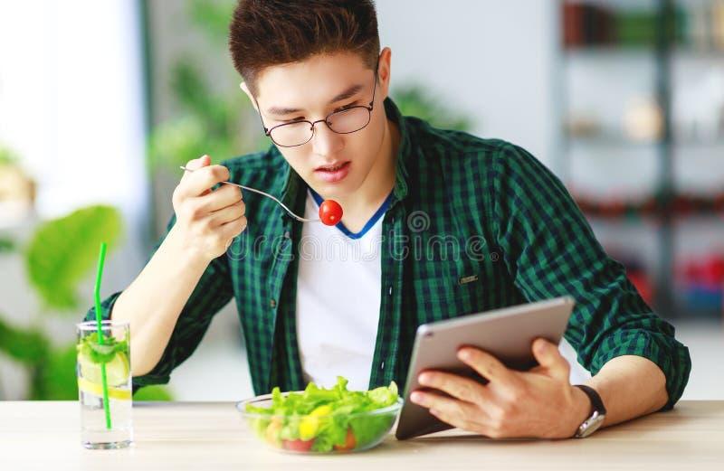 Gesundes Essen glücklicher junger asiatischer Fleisch fressender Salat mit Telefon- und Tabletten-PC am Morgen lizenzfreies stockbild