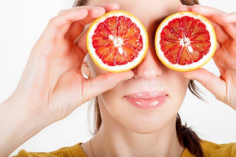 Gesundes Essenkonzept Frohe glückliche junge Frau, die saftiges O hält stockfotografie