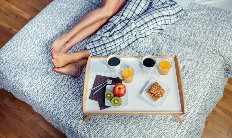 Gesundes Frühstück auf Behälter- und Paarbeinen über Bett lizenzfreies stockfoto