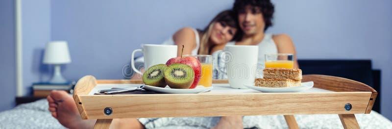 Gesundes Frühstück auf Behälter und Paare, die im Hintergrund liegen stockfotos