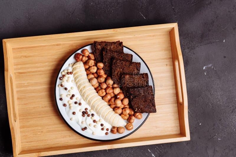Gesundes Frühstück auf dem Küchentisch Rye-Brot, Banane, Körner, Haselnuss und Jogurt auf schwarzem Hintergrund lizenzfreies stockbild