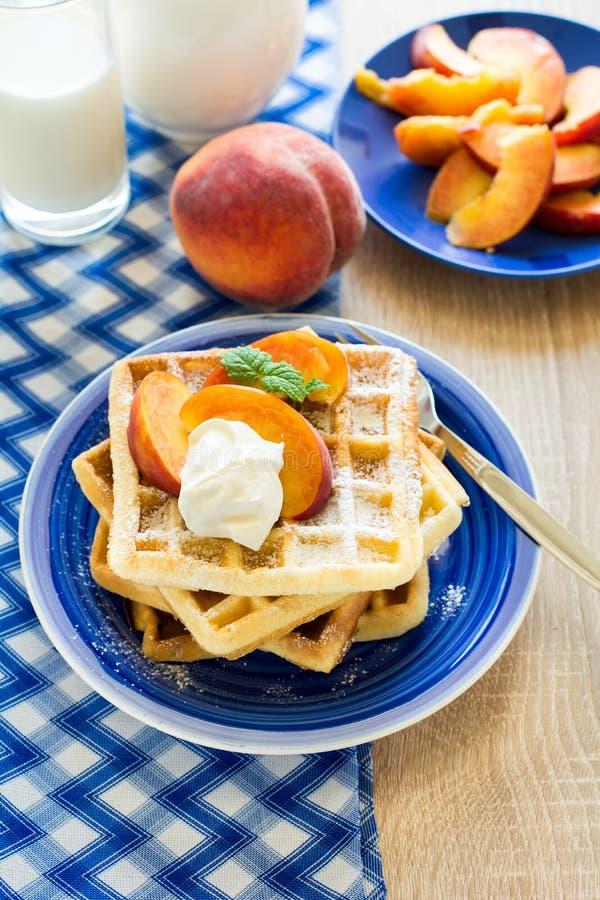 Gesundes Frühstück: Belgische Waffeln mit Pfirsichscheiben und Creme verzierten tadellose Blätter und blaue Serviette stockbild