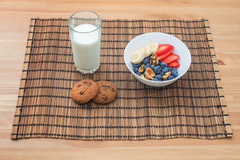 Gesundes Frühstück der Frucht, der Beeren und der Hafermehlplätzchen mit Milch auf einem hölzernen Hintergrund lizenzfreies stockbild