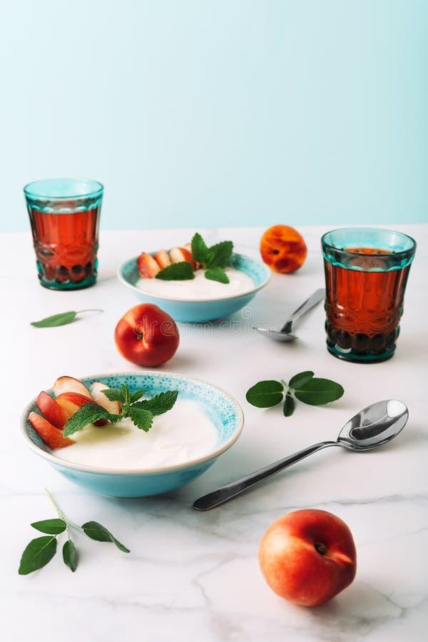 Gesundes Frühstück des natürlichen griechischen Joghurts, der Frucht und des Safts auf Marmortabelle lizenzfreies stockfoto