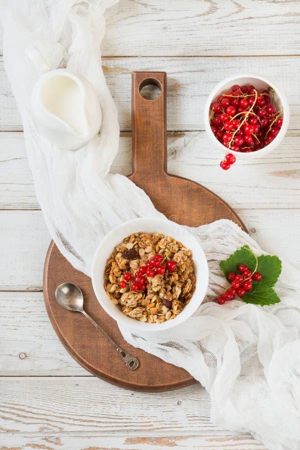 Gesundes Frühstück des Sommers des Granolas, muesli mit Milchkrug mit der roten Johannisbeere geschmückt Beschneidungspfad einges lizenzfreie stockfotografie