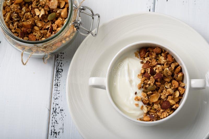 Gesundes Frühstück: Griechischer Jogurt mit selbst gemachtem Granola in einem Weiß stockfotografie