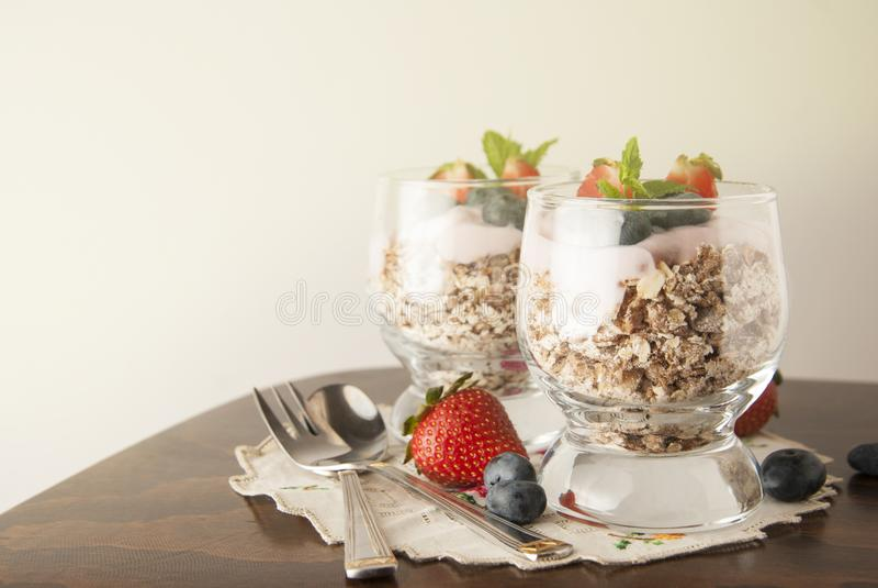 Gesundes Frühstück, Hafermahlzeit mit Früchten: bluebery, strawbery und Minute, Parfait in zwei Gläsern auf einem rustikalen Hint lizenzfreie stockfotos