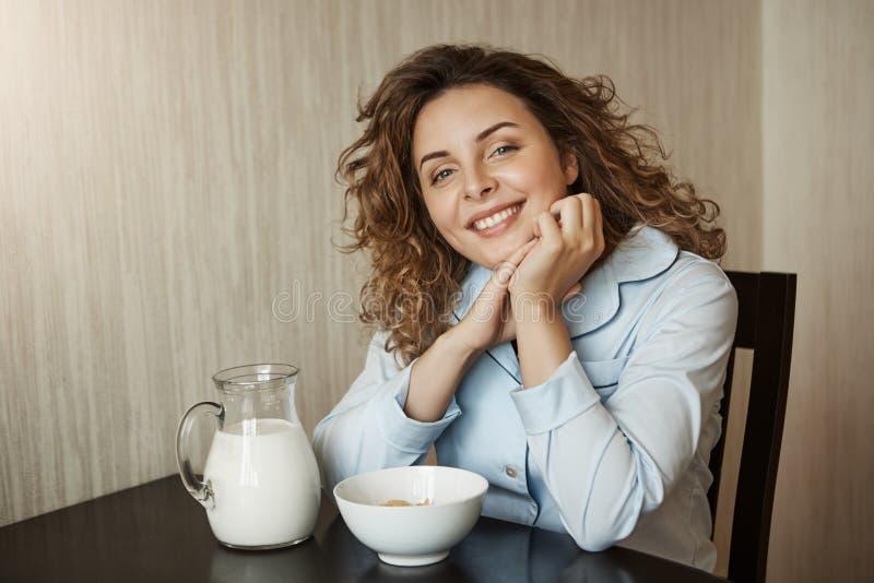 Gesundes Frühstück im Kreis der Familie Schöne junge Mutter mit dem tragenden Nachtzeug des gelockten Haares, das auf Händen währ lizenzfreie stockfotografie