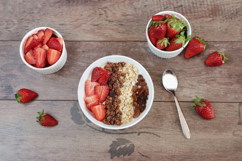 Gesundes Frühstück - Jogurt mit Hafer blättert, Rosinen, Erdbeeren, muesli ab Fruchtfrühstück auf einem hölzernen Hintergrund lizenzfreies stockfoto